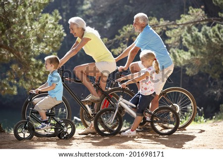 Senior couple with grandchildren on country bike ride - stock photo