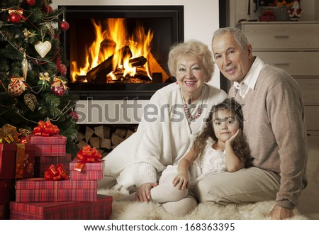 Senior couple with granddaughter in front of fireplace. They are celebrating Christmas holidays  - stock photo