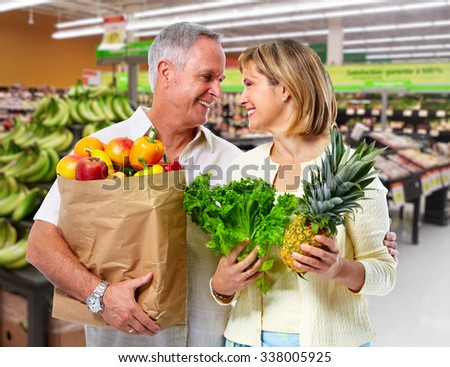 Senior couple with grocery bag of vegetables over market background. - stock photo