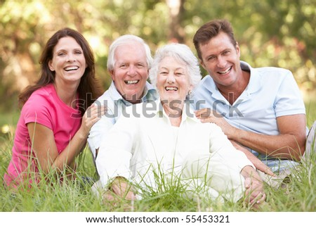 Senior Couple With Grown Up Children In Park - stock photo