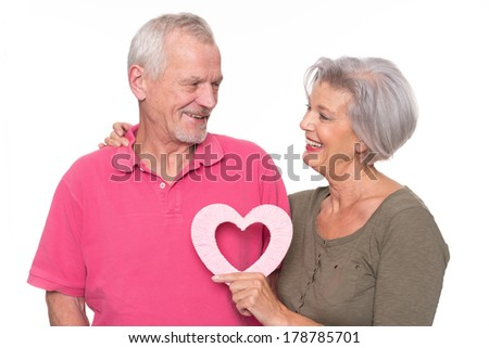 Senior couple with heart in front of white background - stock photo