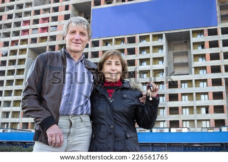 Senior couple with house key in hand against blue blank banner on building - stock photo