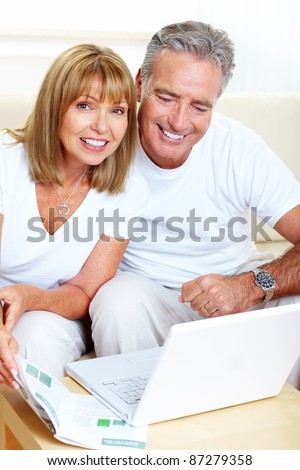 Senior couple with laptop at home. - stock photo