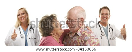 Senior Couple with Medical Doctors or Nurses with Thumbs Up Behind. - stock photo