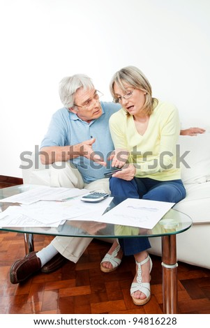 Senior couple with paperwork fighting over money at home - stock photo