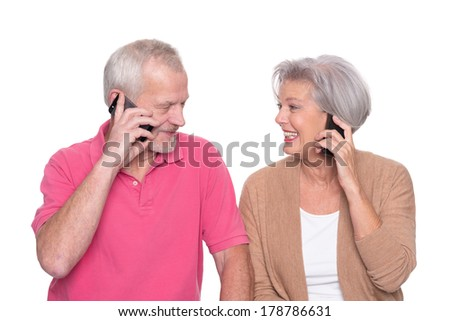 Senior couple with smartphone in front of white background