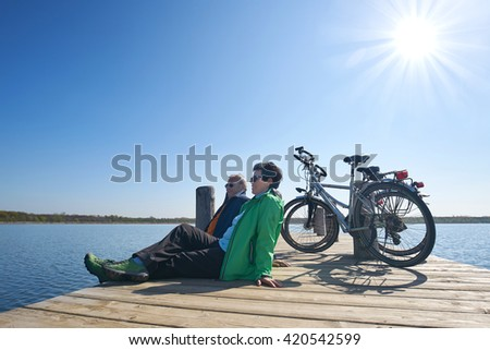 Senior couple with their bikes, Senior woman and man at rest on bike trip sitting on a boardwalk at lake