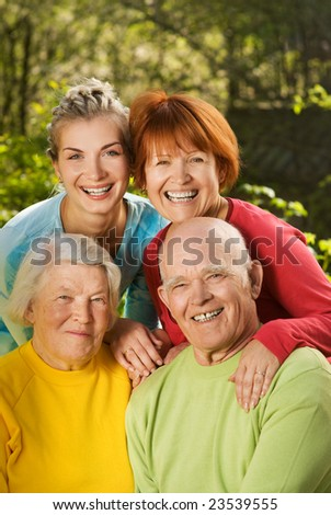 Senior couple with their daughter and granddaughter outdoors - stock photo