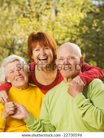 Senior couple with their daughter outdoors - stock photo