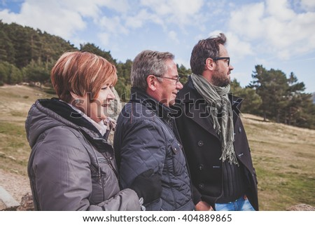 Senior couple with their son taking a walk in the mountain.