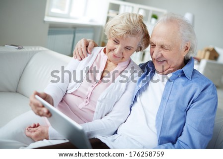 Senior couple with touchpad sitting at home and networking - stock photo