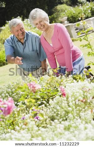 Senior couple working in garden - stock photo