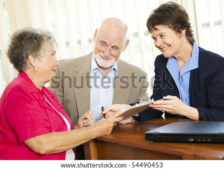 Senior couple working with a broker or adviser, signing paperwork. - stock photo