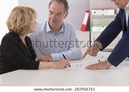 Senior couple writing signature under contract after financial consultation - stock photo