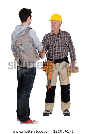 senior craftsman and young apprentice shaking hands - stock photo