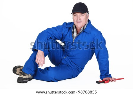 senior craftsman sitting on the floor - stock photo