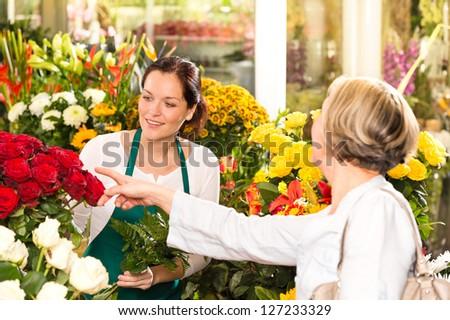 Senior customer buying red roses flower shop florist women working - stock photo