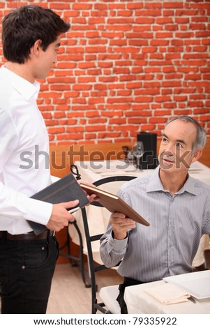 Senior customer ordering in a restaurant - stock photo