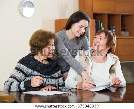Senior cute smiling women making will at public notary office - stock photo