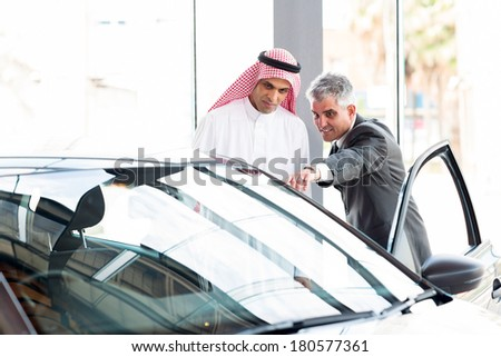 senior dealer pointing car features to potential Arabian buyer - stock photo