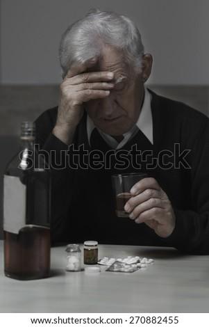 Senior depressed man drinking alcohol and taking drugs - stock photo