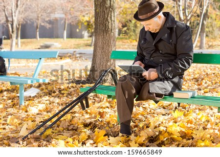 Senior disabled man with one leg surfing the internet on a tablet-pc as he sits in a warm overcoat and hat enjoying a sunny autumn day outdoors in the park - stock photo