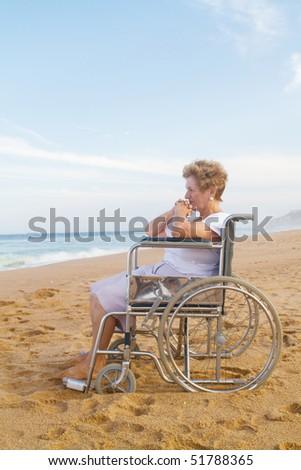 senior disabled woman sitting on wheelchair on beach - stock photo