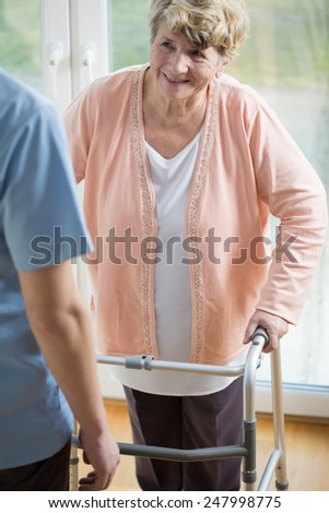 Senior disabled woman with walker talking with her caregiver - stock photo