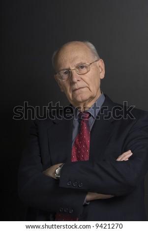 Senior distinguished business man over dark background - stock photo