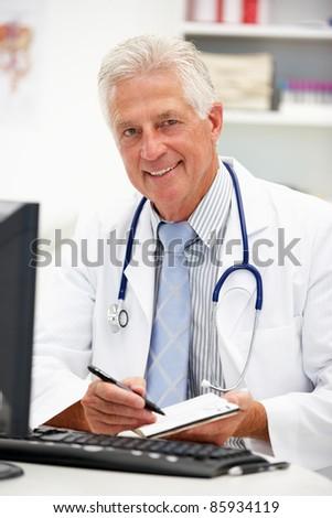 Senior doctor at desk - stock photo