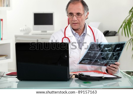 Senior doctor checking an x-ray in his office - stock photo