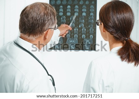 Senior doctor examines MRI image of human head. Senior man doctor teaches young woman doctor - stock photo
