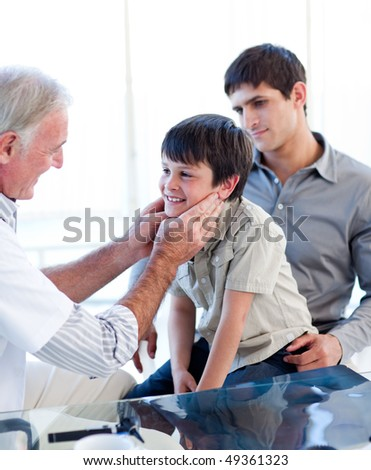 Senior doctor examing little boy throat with his father in the pratice - stock photo