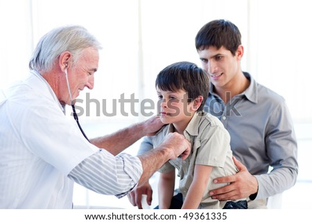 Senior doctor examining a little boy with his father at the practice - stock photo