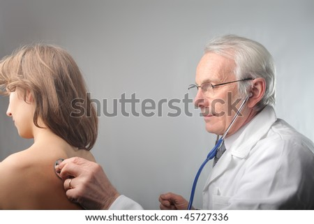 Senior doctor examining a young patient with a stethoscope