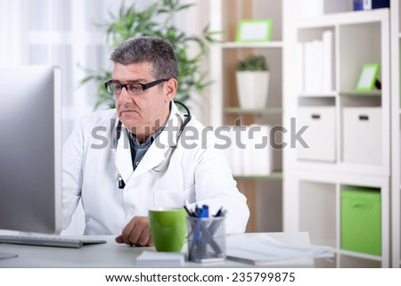 senior doctor in the office working on the computer - stock photo