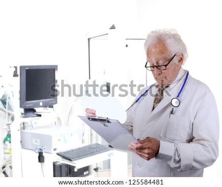 Senior doctor looking at a paper on a clipboard with a pulmonary function lab blurred in the back ground. - stock photo