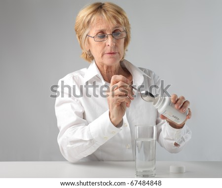 Senior doctor preparing a medicine - stock photo