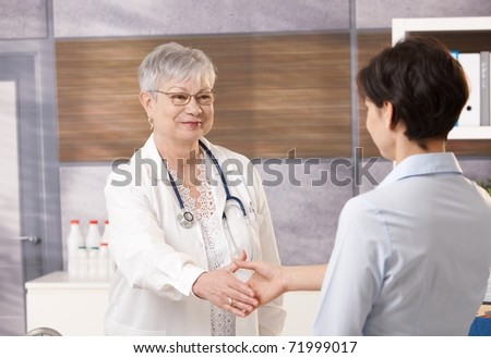 Senior doctor shaking hand with patient in office.? - stock photo