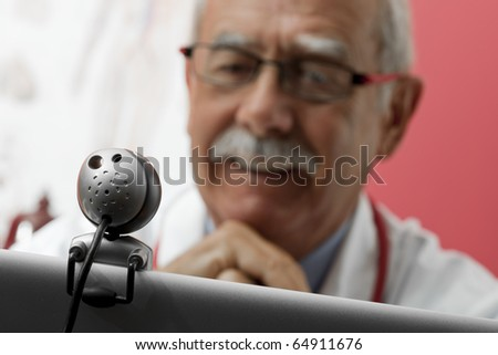 Senior doctor speaking with patient through webcam - stock photo