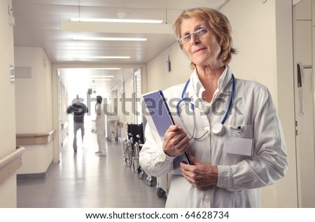 Senior doctor standing in a hospital ward - stock photo