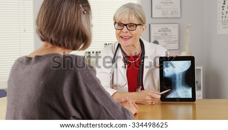 Senior doctor tablet talking x-ray - stock photo