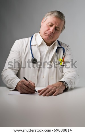Senior doctor writing a prescription - stock photo