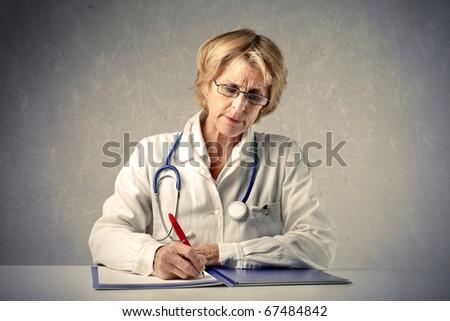 Senior doctor writing on a register - stock photo