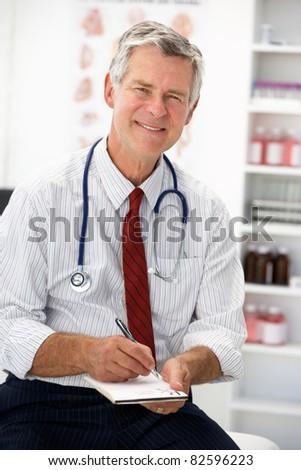 Senior doctor writing prescription - stock photo
