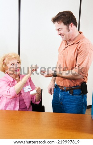Senior election volunteer handing an I Voted sticker to a mid adult man.   - stock photo