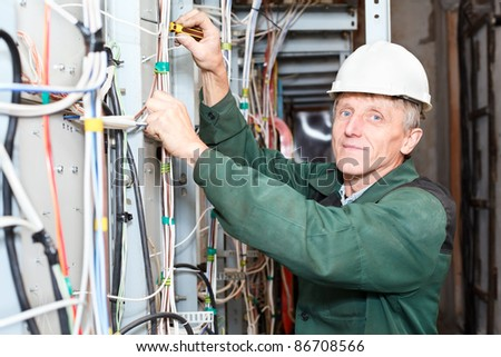 Senior electrician blue eyes working in white hardhat with cables and wires