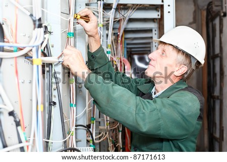 Senior electrician worker inspecting high voltage box in hard hat with screwdriver - stock photo