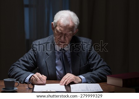 Senior elegant man filling documents in his office - stock photo