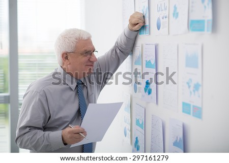 Senior entrepreneur analyzing financial documents on the office wall - stock photo
